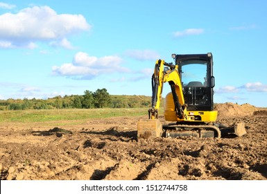 Mini excavator digging earth in a field or forest. Laying underground sewer pipes during the construction of a house. Digging trenches for a gas pipeline or oil pipeline. Earthwork, foundation pit