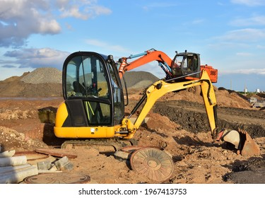 Mini excavator during earthmoving at construction site. Backhoe dig ground for the construction of foundation and laying sewer pipes district heating. Earth-moving heavy equipment on road works
