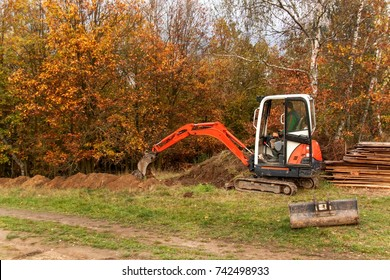 Mini excavator on construction site. Construction of a family house near a forest