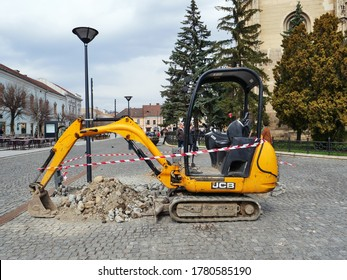 Mini excavator standing idle after digging up the cobblestone pavement in the town center of Cluj-Napoca, Romania on March 30, 2018