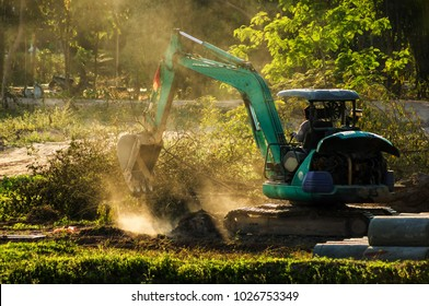 Mini Excavator Working on dusty soil