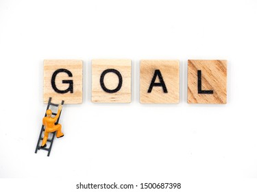 Mini figure of man climbing ladder to the word goal , Business goal concept.