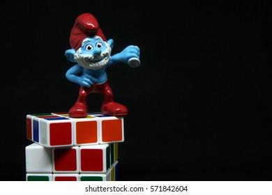 Mini figure of Smurf on black background.