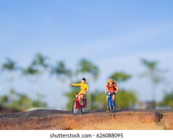 mini figure toys ride bicycle outdoor on the sunny day on blue background of the park