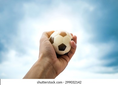 Mini Football in hand on sky , concept of future
