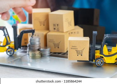 Mini forklift truck load cardboard box with shopping cart symbol and stack of coins behind on laptop keyboard. Logistics and transportation management ideas and Industry business commercial concept.
