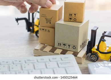 Mini forklift truck load cardboard boxes with symbols on wood pallet and fingers over its and keyboard nearby. Logistics and transportation management ideas and Industry business commercial concept.