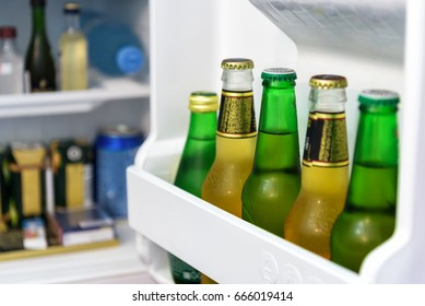 Mini fridge full of bottles of beer, juice and water in a hotel room