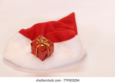 Mini gift box in red reflect gift wrap with golden rope knot and red white christmas hat isolated on white background. It is a thing given willingly to someone without payment, a present.