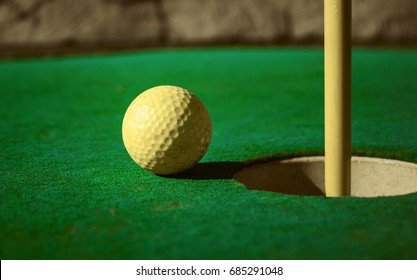 Mini golf ball on green headed towards hole