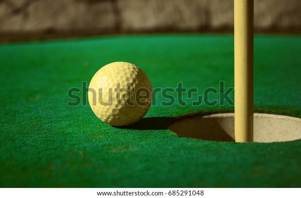 Mini golf ball on green headed towards hole