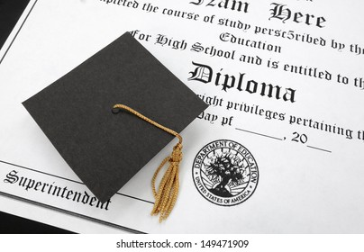 a mini gradaution cap on a high school diploma