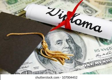 mini graduation cap and diploma on money