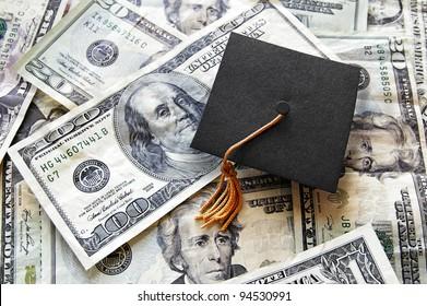 mini graduation cap on top of a pile of cash