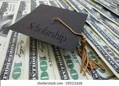 Mini graduation mortar board with Scholarship text, on money