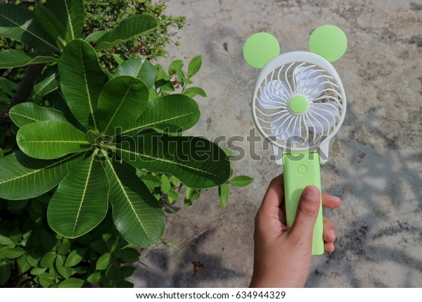 Mini green pastel tone portable electric fan. Hand holding in natural trees green half  grey floor background. Shadow  branches   tree behind.