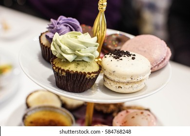 mini green tea cupcakes and oreo macaroons on a dessert stand with afternoon high tea