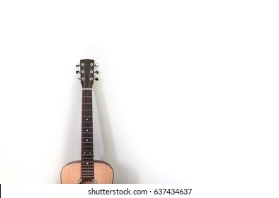 mini guitar lying on the white wall with shade and shadow