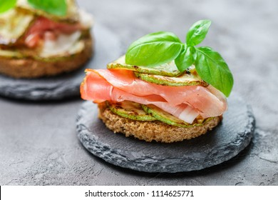 Mini ham (hamon, prosciutto) sandwiches, fried zucchini and Basil close-up on black surface. Gourmet snack. Selective focus