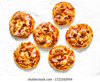Mini ham, tomato sauce, mozzarella pizza on a light background, top view. Delicious breakfast, snack, tapas