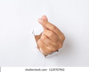 Mini heart hand punching through the paper