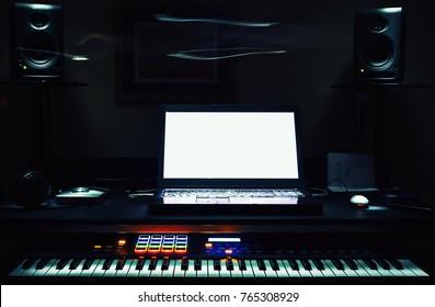 Mini home studio, midi controller and laptop on table.