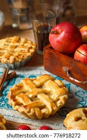 Mini homemade apple pies on rustic background with coffee,cinnamon sticks,apples,vintage towel