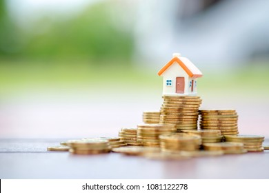 Mini house model on gold stack coins.