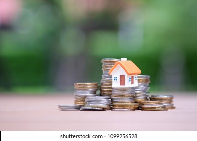 Mini house model on stack of coins with space background. Business, home loan, property management concept.