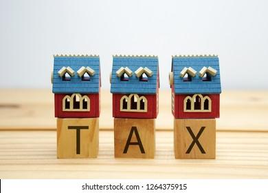 Mini house model over tax word blocks on wooden desk
