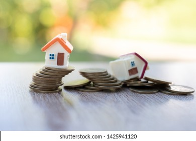 Mini house model and stack of coins. Business risk management. Property investment and house mortgage financial real estate concept