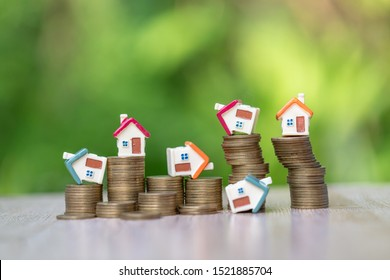Mini house model and stack of coins. Business risk management. Property investment and house mortgage financial real estate concept. Business investment will increase Or bankrupt.