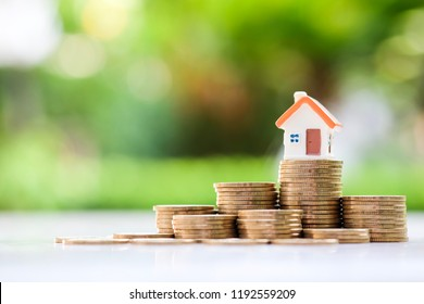 Mini house on stack of coins with green blur background. Investment property concept.