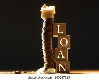 Mini house on stack of coins, wood block with word loan- Concept of Investment property.