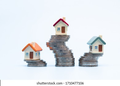 Mini house on stack of coins  on white background., Concept of Investment property, Investment risk and uncertainty in the real estate housing market.
