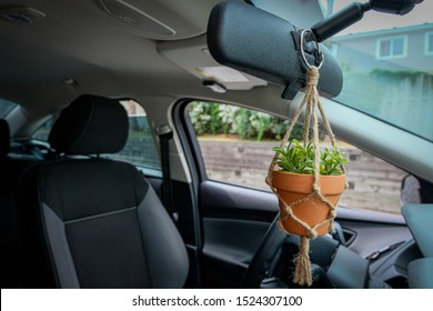 A mini macrame plant hanger made out of jute twine is hanging from a rear view mirror in a car. A fake plant is in the ceramic pot.