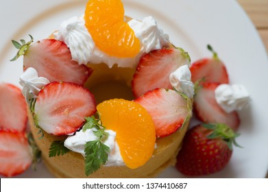 mini mascarpone chiffon cake topped with whipped cream, orange and strawberries