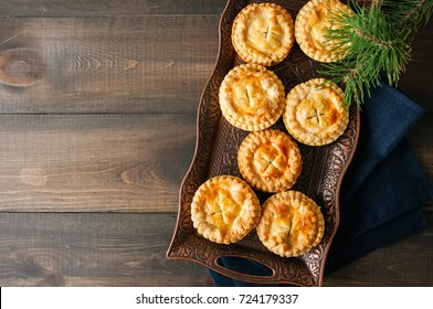 Mini meat pies from flaky dough on a vintage tray over wooden background.