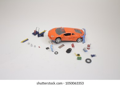 mini mechanics replacing a punctured tyre of a car