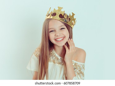 Mini Miss. Young happy girl with a cute smiling laughing wearing a crown and a white dress on Holiday looking at you camera isolated green background