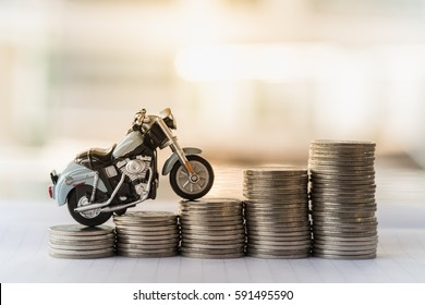 Mini motorcycle model on stack of coins. Saving, Finance, Loan and leasing Concept.
