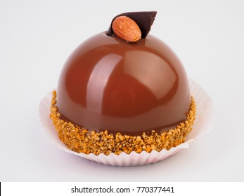 Mini mousse pastry dessert covered with chocolate velour and decorated with brown glaze and almond isolated on white background. Modern european cake. French cuisine.