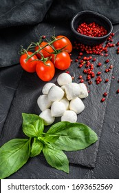 Mini mozzarella cheese, Basil leaves and cherry tomatoes, cooking Caprese salad. black background. top view