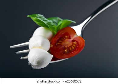 Mini mozzarella cheese with tomato cherry and green basil leaves on a fork . Healthy Mediterranean food.