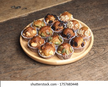 Mini muffins with variety of toppings on wooden plate