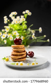 mini pancakes with fruit and varenie on a plate with cherries and camomiles in the background. Vertical orientation - Shutterstock ID 1779668960