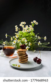 mini pancakes with fruit and varenie on a plate with cherries and camomiles in the background. Vertical orientation - Shutterstock ID 1779668963