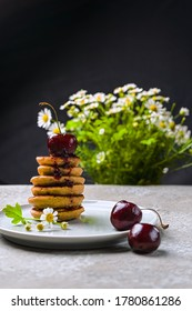 mini pancakes with fruit and varenie on a plate with cherries and camomiles in the background. Vertical orientation - Shutterstock ID 1780861286