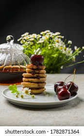 mini pancakes with fruit and varenie on a plate with cherries and camomiles in the background. - Shutterstock ID 1782871364