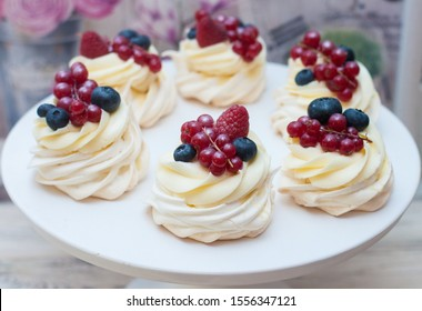 Mini pavlova cakes with cream cheese frosting and fresh berries, blueberries, raspberries and strawberries on white cake stand.